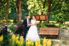 Beautiful couple walking in the park in their wedding day. Stock Photo