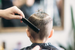 Little Boy Getting Haircut By Barber While Sitting In Chair At Barbershop. Stock Photo