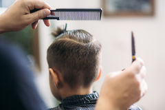Little Boy Getting Haircut By Barber While Sitting In Chair At Barbershop. Stock Photos