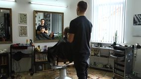 Little boy getting haircut by barber while sitting in chair at barbershop. stock footage