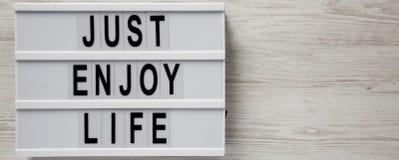 'Geniet enkel van het levens 'woorden op moderne raad op een witte houten oppervlakte, hoogste mening De ruimte van het exemplaar royalty-vrije stock fotografie