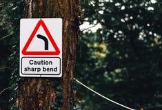 """""""Знак изгиба под острым углом предосторежения """"повиснул вверх на дереве в Великобритании в лесе стоковое фото rf"""