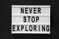"""""""Никогда не останавливайте исследовать """"слово на современной доске над черной поверхностью, взглядом сверху Надземное, плоское по стоковые изображения"""