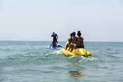 Banana boat in blue sea and clear sky. ‎Laem Mae Pim Beach February 25, 2013: Unidentified tourist are playing banana boat at Leam Mae Pim Beach Thailand stock photos