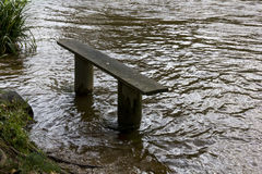 'The Wet Seat' - Riverside Bench Besides the Flooded River Torridge, Torrington, Devon, England. View looking at a flooded bench beside the River Stock Photos