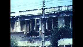 1963 – Traffic in front of a destroyed building in Vietnam. Vietnam War. Civil Live. Traffic in front of a destroyed building in Viatnam stock footage