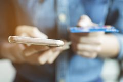 â€拿着手机和信用卡的妇女的‹手对在网上付钱 免版税图库摄影