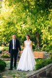 Beautiful par som går i parkera i deras bröllopdag Arkivfoto