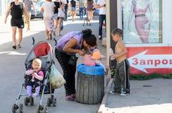 € de KIEV, UKRAINE «le 8 septembre 2016 : Femme avec trois petits enfants recherchant la nourriture dans le panier de rebut prè Photo stock