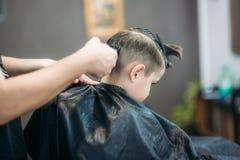 Littlepojke som får frisyr av Barber While Sitting In Chair på frisersalongen  Arkivfoto