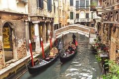 "€ Venedigs, Italien ""am 21. Dezember 2015: Venetianischer Gondoliere, der Gondel mit Touristen durch Kanal stochert Venedig Ital Lizenzfreies Stockfoto"