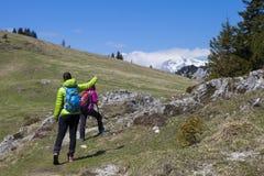 """€ wandern """"Wanderer, die auf Wanderung in der Gebirgsnatur gehen und auf Bergspitze, am sonnigen Tag zeigen Lizenzfreie Stockbilder"""