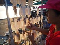 Â女性摊贩卖各式各样的乌贼格栅 免版税库存图片