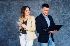 γυναίκα και άνδρας επιχειρηματιών που στέκονται απέναντι από τον γκρίζο τοίχο και που κρατούν την ταμπλέτα και το lap-top Στοκ Εικόνα