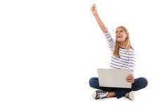 excitó a la muchacha adolescente que se sentaba en el piso, celebrando éxito con un brazo aumentado, aislado Fotografía de archivo