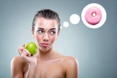 het Dieet! Vrouw die een appel eten, maar hij denkt een doughnut stock fotografie