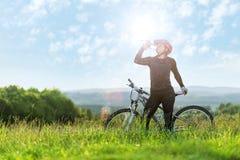 Â-Sport-Fahrradfrau, trinkend auf einer Wiese, schöne Landschaft Stockfotos