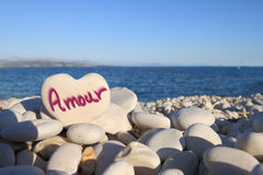 âAmourâ écrit sur la pierre en forme de coeur Image stock