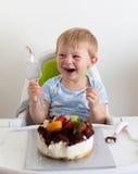 Âgé de deux ans adorable mangeant son gâteau d'anniversaire Images stock