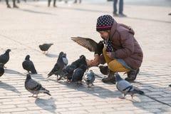 Âge de fille 6-8 ans alimentant des pigeons à la place principale dans la vieille ville Images libres de droits
