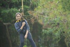 Âge de l'adolescence asiatique accrochant sur la corde de sécurité dans l'acti extérieur d'aventure Photographie stock