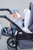 Âge heureux de bébé de 9 mois sur la voiture d'enfant Photographie stock libre de droits