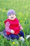 Âge heureux de bébé garçon de 8 mois se reposant sur l'herbe Image libre de droits