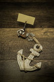 Âncora branca velha com o grampo de madeira da forma do calamar e pedaço de papel vazio Foto de Stock