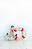Âncora e boia de vida em um assoalho de madeira branco Fotografia de Stock Royalty Free
