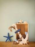 Âncora e shell de madeira náuticos velhos na tabela de madeira sobre o fundo de madeira do aqua Fotografia de Stock