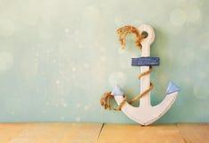 Âncora náutica velha na tabela de madeira sobre o fundo do aqua e a folha de prova de madeira do brilho Foto de Stock Royalty Free