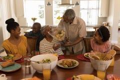 Älterer Mann, der der älteren Frau auf Speisetische Blumenblumenstrauß gibt stockbilder