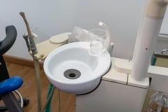 Ärztlicher Dienst von Zahnheilkunde, Werkzeugzahnarzt Clear-Plastiktasse wasser auf Wanne lizenzfreies stockbild