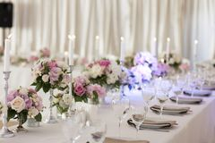 ПÐΜÑ€ÐΜÐ ² ÐΜÑ  Ñ 'и Ð ² GoogleBingFlower przygotowania są na stole zakrywającym z białym tablecloth Srebni candlesticks zdjęcie stock