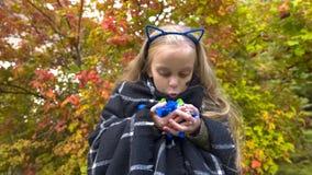 Überglückliches Mädchen, das Süßigkeiten, das lustige Gesicht machend hält und genießen Halloween-Feiertag lizenzfreie stockfotos