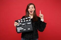 Überraschte junge Frau in der schwarzen Pelzstrickjacke, die Zeigefinger mit großer neuer Idee, klassische schwarze Filmherstellu stockbild