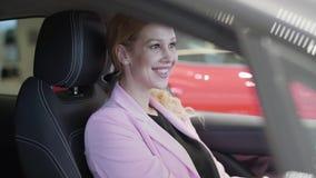 Überzeugte lächelnde Frau in der rosa Jacke im Auto, schauend im Rückspiegel und schicken Luftkuß zu ihrer Reflexion stock video
