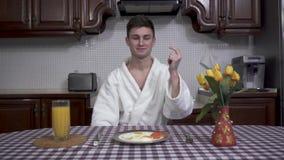 Überzeugter lächelnder Mann in weißen Bademantel snapps seine Finger und Tabelle mit Frühstück erscheint vor ihm Überziehen Sie m stock video footage