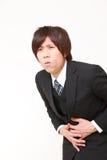 〕年轻日本商人遭受stomachache 免版税库存照片