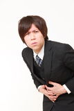 〕el hombre de negocios japonés joven sufre del dolor de estómago Foto de archivo libre de regalías