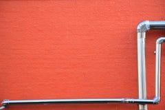 Pipes en una pared roja Imágenes de archivo libres de regalías