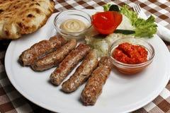 Čevapčiči with lepinja and vegetables Royalty Free Stock Image