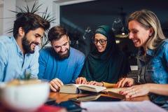不同种族在家学会的学生 学会和为大学检查,选择聚焦做准备 免版税图库摄影