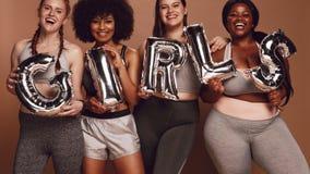 不同的小组有女孩词的妇女在气球信件 免版税库存图片