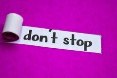 不要停止文本,启发、刺激和企业概念在紫色被撕毁的纸 库存照片
