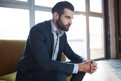 丢失在企业想法 周道的英俊的年轻商人考虑事务,当坐沙发时 库存照片