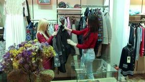 两个女孩在时尚商店在一个大购物中心买新的衣裳 影视素材
