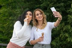 两个女孩采取selfies并且吃着冰淇淋 库存图片