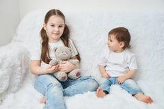 两个孩子,姐妹坐在白色T恤和蓝色牛仔裤的一个白色沙发 软的豪华的熊 免版税库存照片