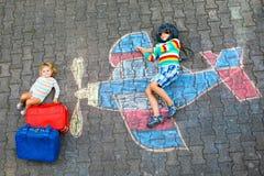两个小孩、孩子的男孩和获得小孩的女孩与与飞机图片图画的乐趣与五颜六色的白垩  免版税库存照片